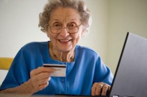 Ältere Frau bezahlt online mit Kreditkarte